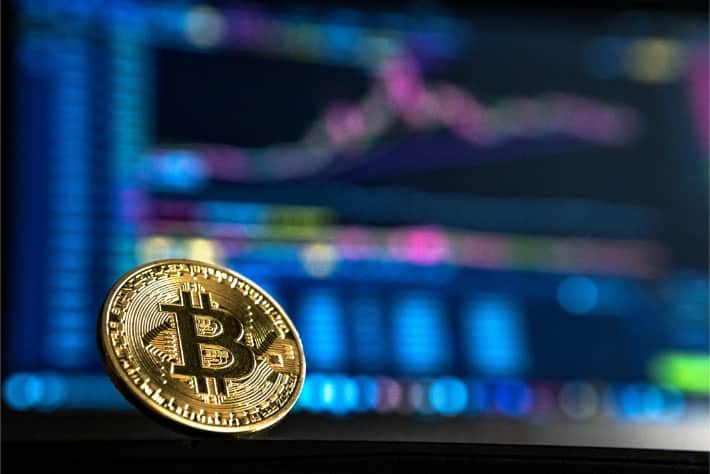 Bitcoin in front of a laptop screen representing the ransom demanded in WannaCry ransomware attack